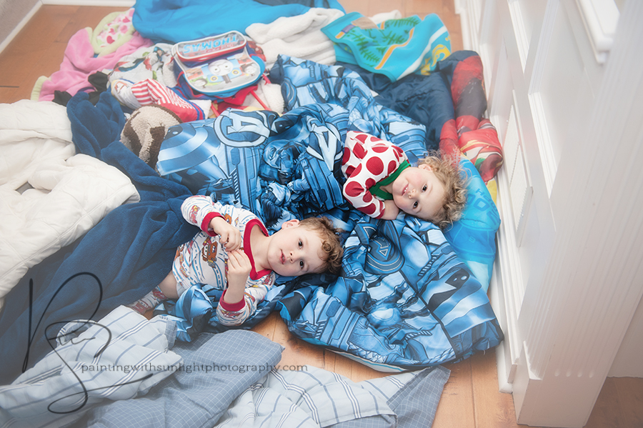 Children playing in a colorful mess of blankets