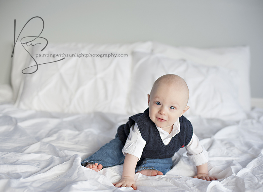 6 month old baby on white bed